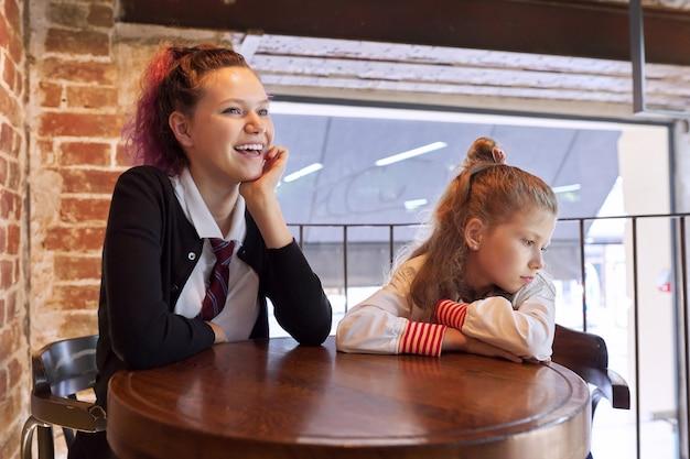 Kinderen, twee zussen, tiener en jongere zus, zitten samen in café aan tafel. meisjes rusten na school