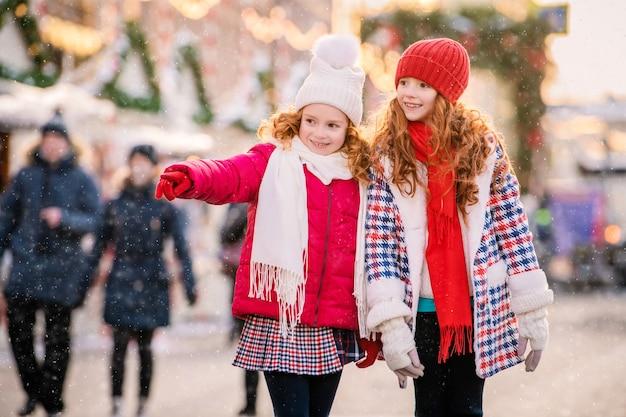 Kinderen van roodharige zussen lopen op een feestelijk versierde kerstmarkt in de stad.