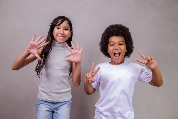Kinderen van verschillende diversiteit op grijze achtergrond. japans meisje met een afrokind op grijze achtergrond met ruimte voor tekst.