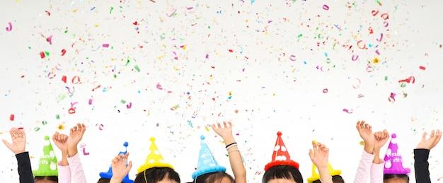 Kinderen verhogen handen in partij geniet van het gooien van kleurrijke confetti in kerstmis nieuwjaar
