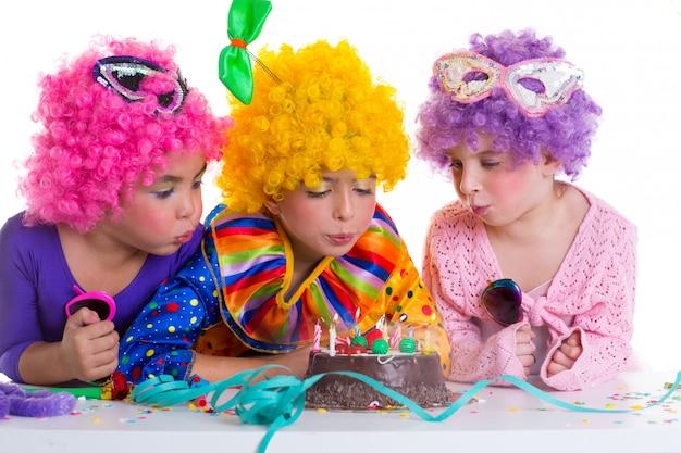 Kinderen verjaardagsfeestje clown pruiken blaast cake kaarsen