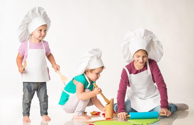 Kinderen verkleed als koks bereiden gebakjes