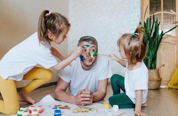 Kinderen vermaken zich met hun vader meisjes tekenen op de huid van het gezicht van een man met kleurrijke verf creativiteit en verbeelding vaderdag en het concept van de familie lichaamskunst en schilderen