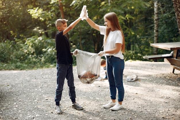 Kinderen verzamelt afval in vuilniszakken in park
