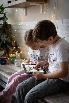 Kinderen videobellen elkaar om in contact te blijven tijdens de winterstop. kleine jongen met kerstmuts zit voor een computerscherm, online chatten met een groep van zijn diverse vrienden op kerstavond thuis