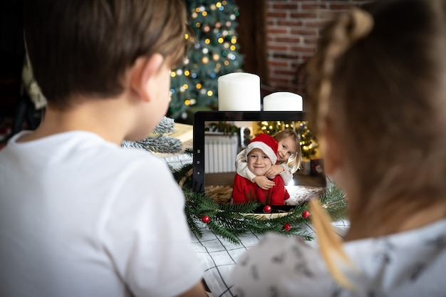 Kinderen videobellen winter kleine jongen kerstmuts computerscherm online chatten kerstavond thuis