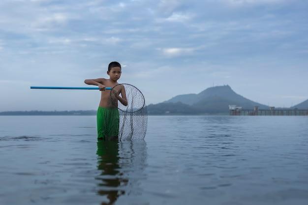 Kinderen vissers werpen nog steeds vissersdorpjes. vissen op zee zwemmen en vissen uitrusting. blij de glimlachen van de kinderen. de vissers zullen werpen op de oude houten boot een mooie ochtend zonsopgang.