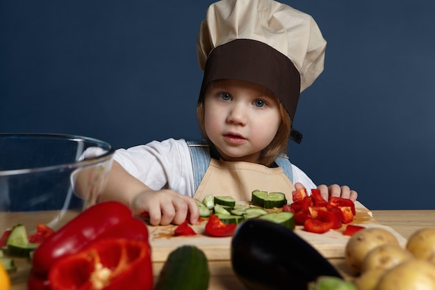 Kinderen, voedsel, voeding en een gezond levensstijlconcept. schattige vrolijke 5-jarige babymeisje in uniform chef-kok verschillende groenten snijden op koken bord tijdens het maken van vegetarische lasagne of soep