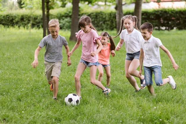 Kinderen voetballen op gras