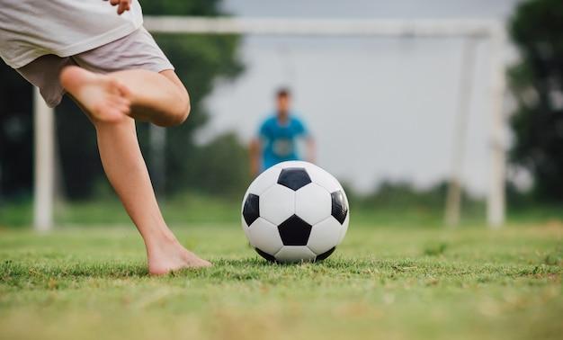 Kinderen voetballen voetbal om te oefenen op het groene grasveld