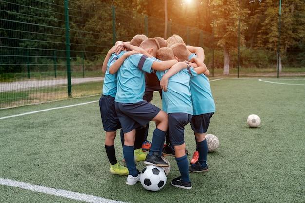 Kinderen voetbalteam en coach knuffelen elkaar op voetbalveld voor wedstrijd