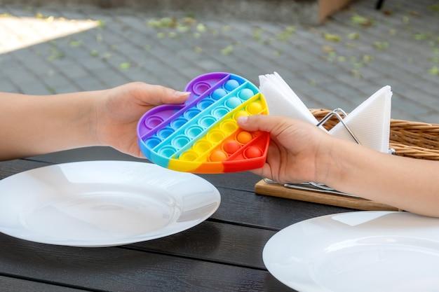 Kinderen wachten op bediening in een restaurant terwijl ze buiten spelen met een siliconen hartvormig speelgoed. handen houden een pop-it-speeltje boven de tafel in een café.