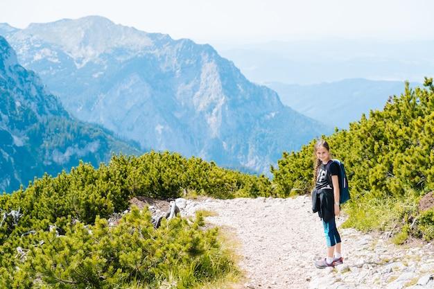 Kinderen wandelen op een mooie zomerdag in de bergen van de alpen, oostenrijk, rusten op een rots en bewonderen een prachtig uitzicht op de bergtoppen. actieve gezinsvakantie met kinderen. buitenshuis plezier en gezonde activiteit.