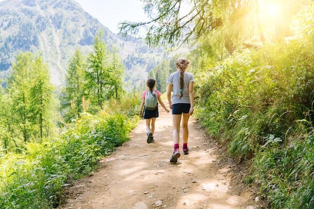 Kinderen wandelen op een mooie zomerdag in de bergen van de alpen, oostenrijk, rusten op een rots en bewonderen een prachtig uitzicht op de bergtoppen.