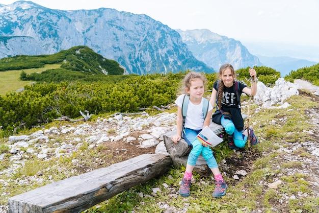 Kinderen wandelen op een mooie zomerdag in de bergen van de alpen