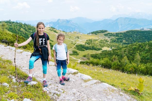 Kinderen wandelen op mooie zomerdag in de bergen van de alpen, oostenrijk