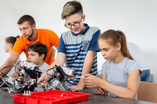 Kinderen werken met leraar aan hun robot-onderwijsproject