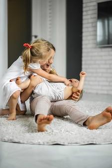 Kinderen woeden, broers en zussen brengen samen tijd door, knuffelen, lachen.