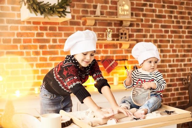 Kinderen worden gekookt en gespeeld met meel en deeg in de keuken