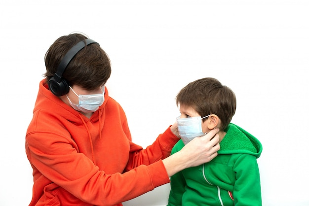 Kinderen zetten een medisch masker op in lichte kleding. coronavirusbescherming