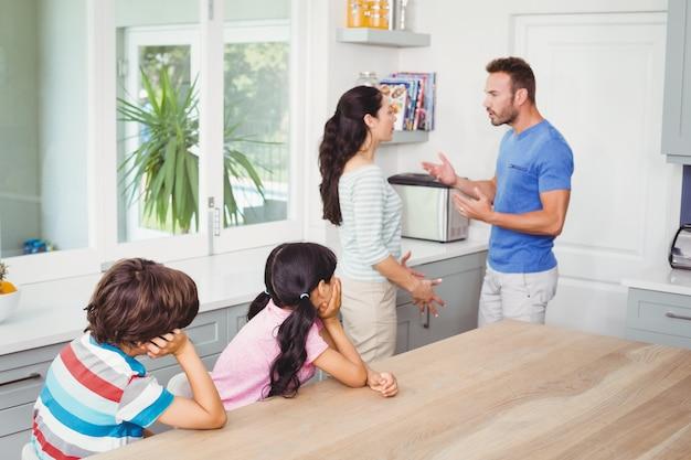 Kinderen zitten aan tafel met ouders ruzie