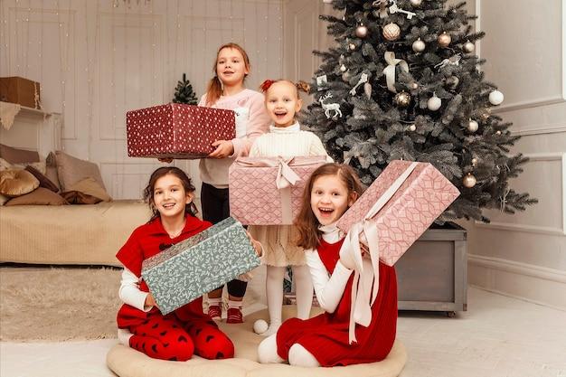 Kinderen zitten bij de kerstboom en pakken cadeautjes uit