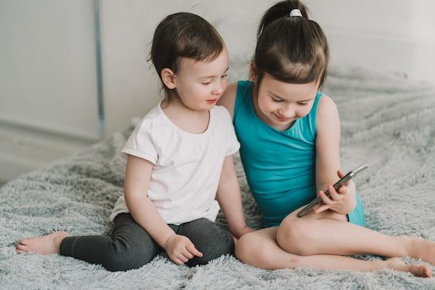 Kinderen zitten en kijken naar de telefoon de verslaving van kinderen aan gadgets online leren voor kleuters