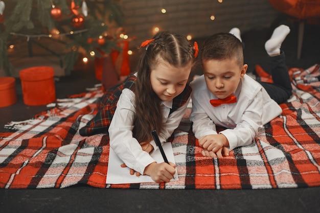 Kinderen zitten in de buurt van de kerstboom. kinderen schrijven een brief aan de kerstman.