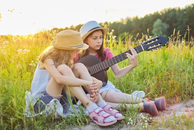 Kinderen zitten in de natuur met klassieke gitaar