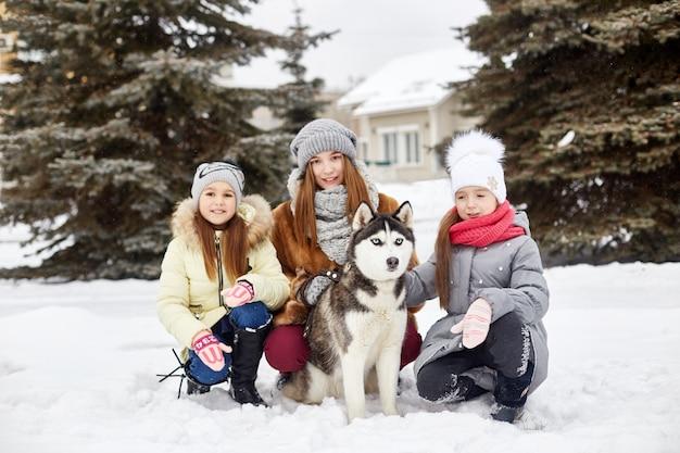 Kinderen zitten in de sneeuw en aaien hond husky