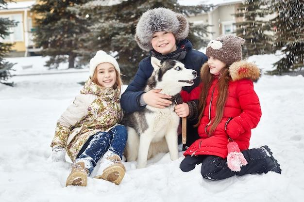 Kinderen zitten in de sneeuw en streelden hond husky. kinderen gaan in de winter uit met husky's