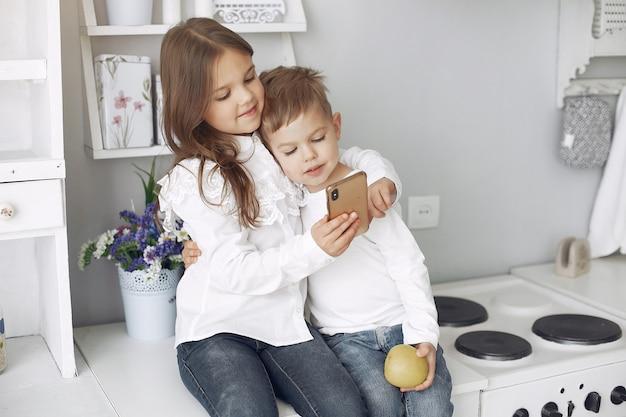 Kinderen zitten in een keuken thuis