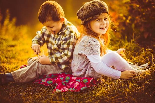 Kinderen zitten naast elkaar op een plaid
