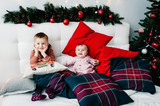 Kinderen zitten op bed in de buurt van de kerstboom