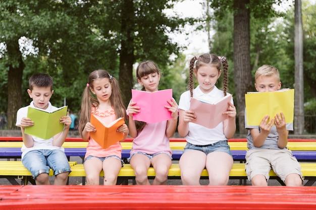 Kinderen zitten op een bankje en lezen