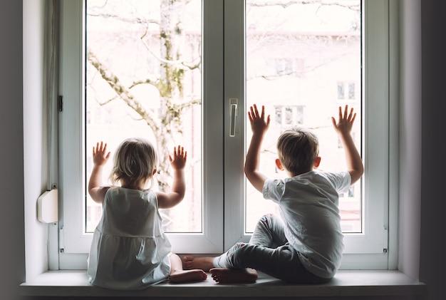Kinderen zitten thuis in quarantaine en kijken uit het raam quarantaine pandemie coronavirus covid19