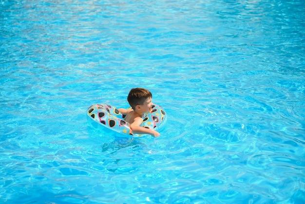 Kinderen zomervakantie. kind zwemmen in zwembad. kinderen hebben plezier in het aquapark.