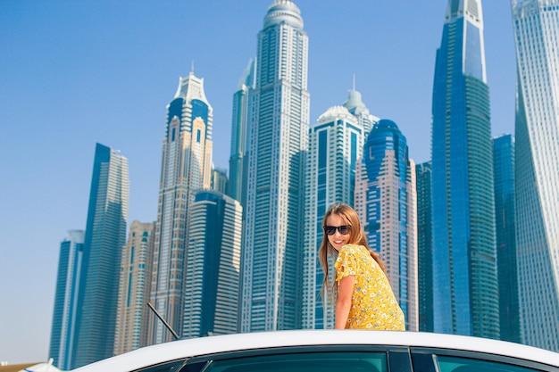 Kinderen zomervakantie. tienermeisje op autovakantie boven wolkenkrabbers in dubai