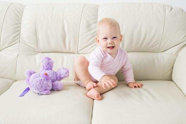Kinderen, zuigelingen en jeugdconcept - mooie schattige zachte baby zittend op de bank