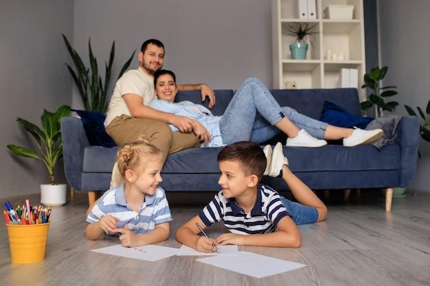 Kinderen zus en broer samen tekenen op de vloer terwijl jonge ouders thuis ontspannen op de bank, jongetje meisje plezier, broers en zussen vriendschap, familie vrijetijdsbesteding in de woonkamer