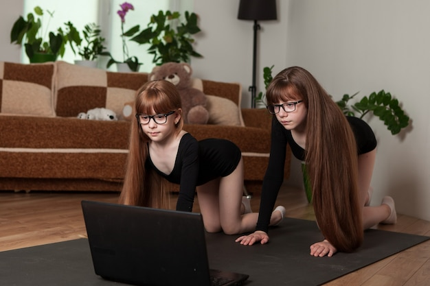 Kinderen, zusjes, trainen thuis op de gymnastiekmat.