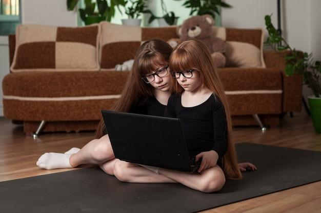 Kinderen, zusjes, trainen thuis op de gymnastiekmat