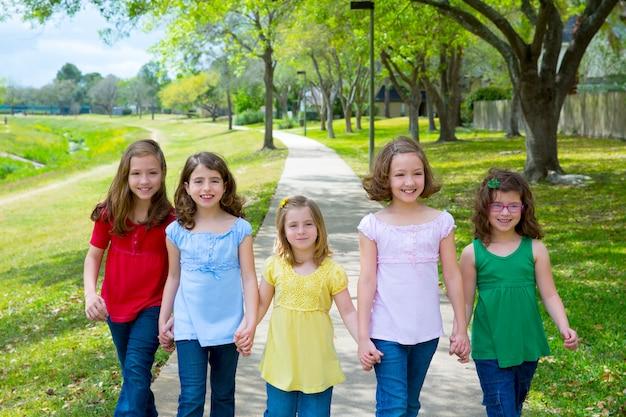 Kinderengroep zustersmeisjes en vrienden die in park lopen