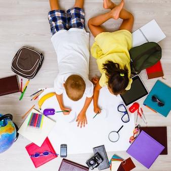 Kinderenjongen en meisje die samen tekening spelen die op de vloer liggen, hoogste mening