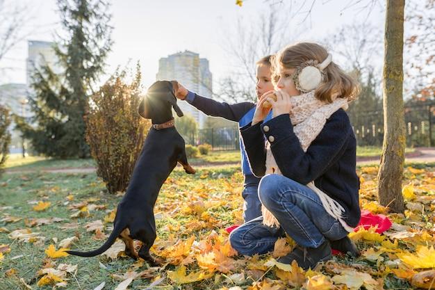 Kinderenjongen en meisje het spelen met tekkelhond