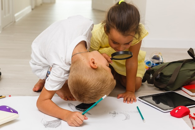 Kinderenjongen en meisjestekening het spelen met vergrootglas