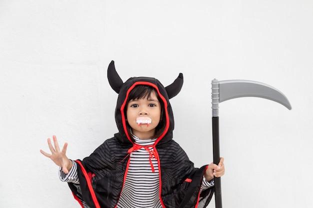 Kinderenmeisje die geheimzinnige halloween-kleding dragen die een sikkel op witte achtergrond houden