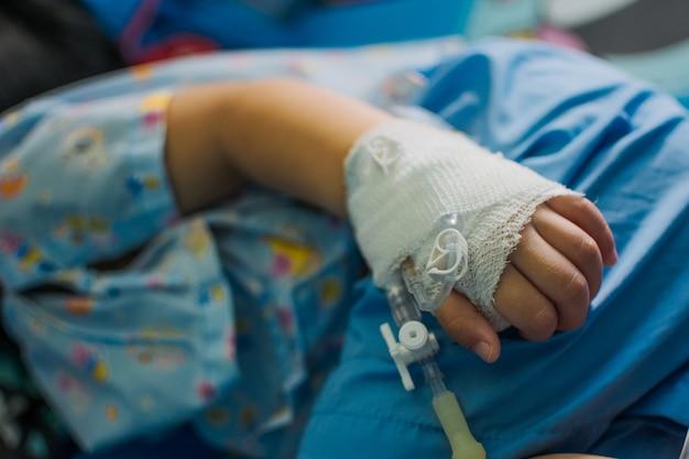 Kinderenmeisje op een druppel die een zoute oplossing in het ziekenhuis ontvangt.