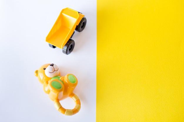 Kinderenspeelgoed op witte en gele achtergrond.