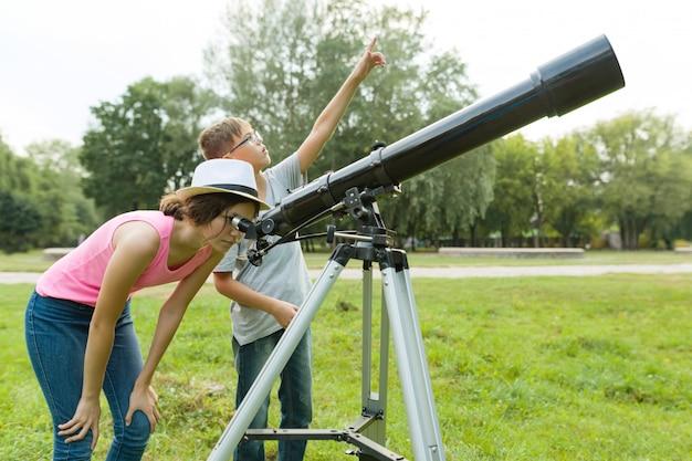 Kinderentieners in het park die door een telescoop kijken